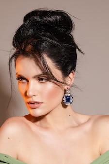Довольно элегантная женская модель с красивой укладкой позирует в студии. концепция красоты
