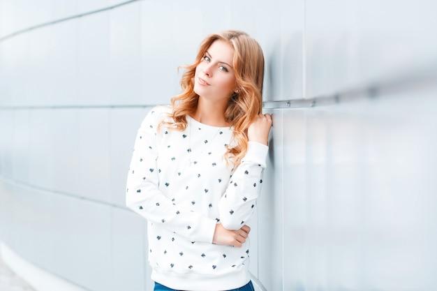 屋内の白いモダンな壁の近くのファッショナブルなプルオーバーで美しい笑顔でかなりエレガントなポジティブな若いブロンドの女性