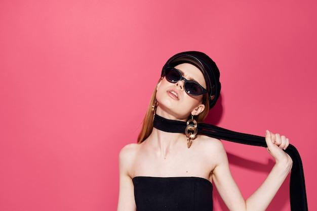 Pretty elegant woman jewelry accessories dark glasses studio pink background.