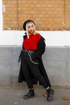 革のブーツのベレー帽の赤いシャツのトレンディなパンツでファッショナブルなコートを着たかなりエレガントな若いブロンドの女性は、秋の日にヴィンテージのレンガの壁の近くに立って休んでいます