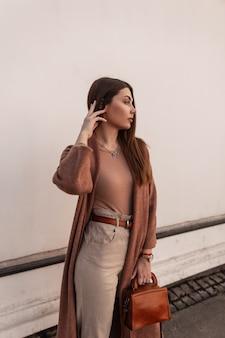가죽 세련 된 갈색 핸드백 거리에 흰색 건물 근처 포즈와 바지에 세련 된 코트에 꽤 우아한 젊은 여자. 현대 빈티지 매력적인 여자는 도시에 산책. 봄 캐주얼 트렌디 룩
