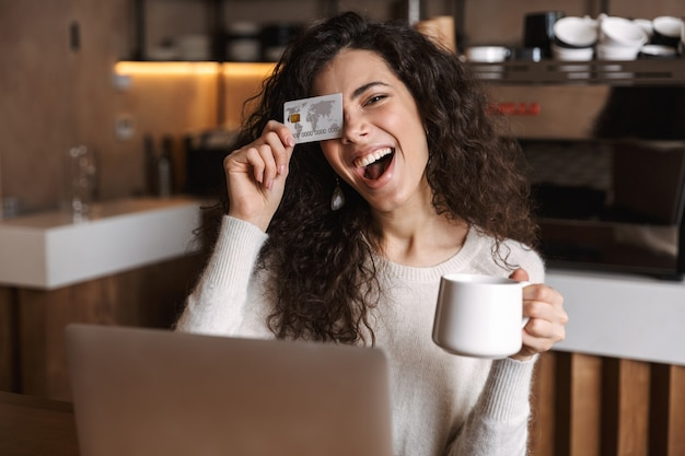 Pretty emotional girl sitting in cafe using laptop computer holding credit card