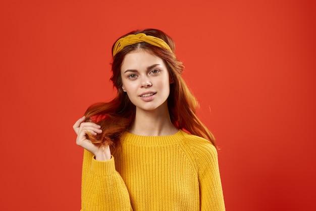 彼女の髪を保持しているかなり感情的な女性。黄色のセーターファッション赤い背景。