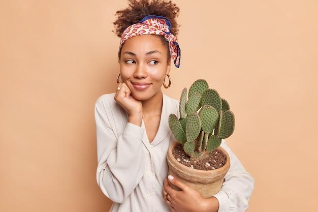 꿈결 같은 표정의 곱슬머리를 가진 예쁜 민족 여성이 화분에 담긴 선인장을 멀리 바라보고 있으며 베이지색 벽에 격리된 세련된 옷을 입은 손가락으로 선인장을 만지고 싶어합니다.