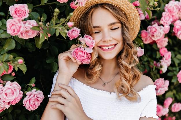 Довольно европейская девушка улыбается с закрытыми глазами на природе. красивая светловолосая женщина наслаждается фотосессией с цветами.