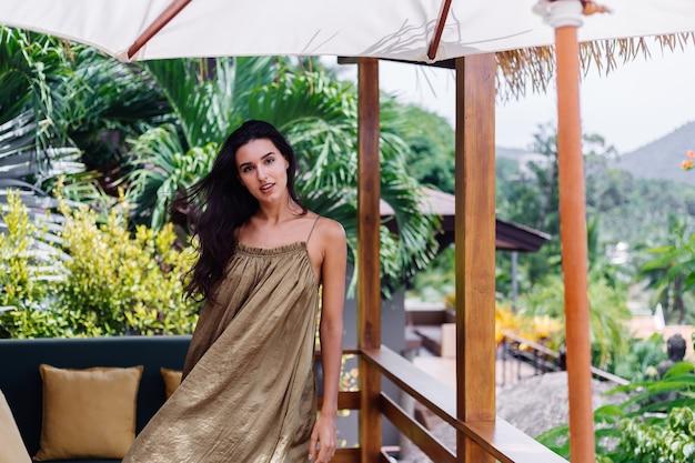 美しい休暇を楽しんでいる別荘のテラスで自然光で夏の空飛ぶドレス、熱帯の枕と屋外ソファでかなりヨーロッパのポジティブな笑顔の女性