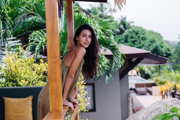 Довольно европейская позитивная улыбающаяся женщина в летнем летающем платье при естественном дневном свете на террасе виллы, наслаждаясь красивым отдыхом, на открытом воздухе на диване с подушками на тропическом