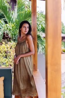 Donna sorridente positiva abbastanza europea in vestito da volo estivo alla luce del giorno naturale sulla terrazza della villa godendo di una bella vacanza, divano all'aperto con cuscini su tropicale