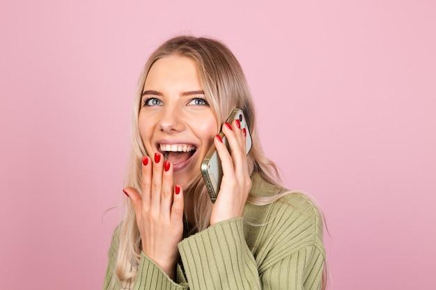Donna abbastanza europea in maglione lavorato a maglia casual sulla parete rosa