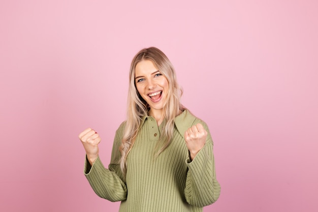 Pretty european woman in casual knitted sweater on pink wall