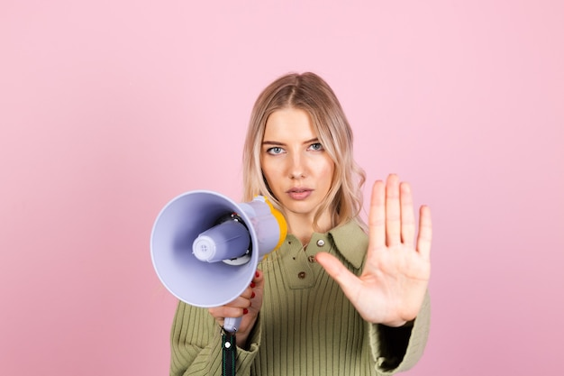 Pretty european woman in casual sweater on pink wall. unhappy serious with megaphone doing stop sign with palm of the hand