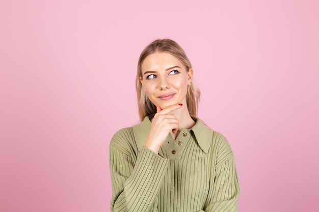 Pretty european woman in casual sweater on pink wall