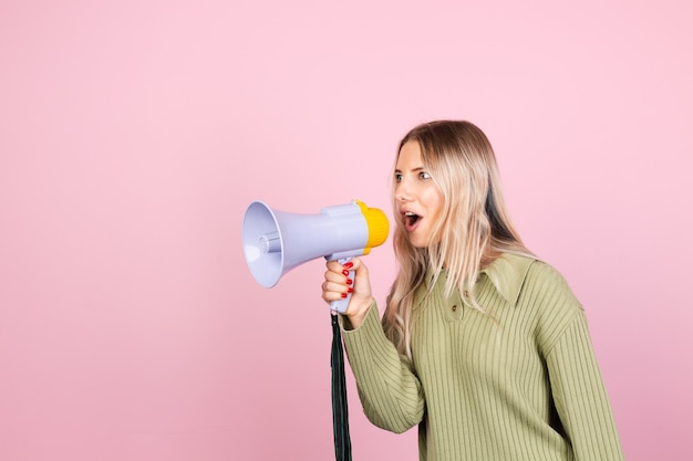 Donna abbastanza europea in maglione casual con megafono sulla parete rosa