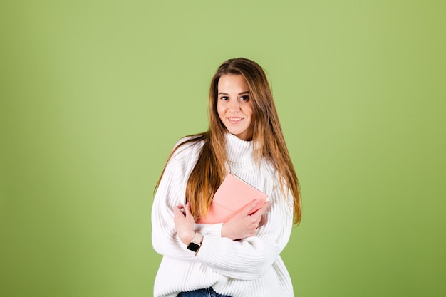 Pretty european woman in casual white sweater isolated, cute positive holding notepad