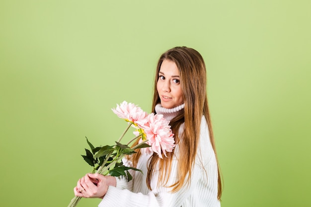 Pretty european woman in casual white sweater isolated, romantic look holding bouquet of pink flowers with smile
