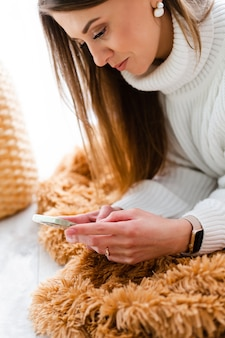 Pretty european woman in casual white sweater lies on floor at home by window with phone, positive chatting, having conversation, send text message