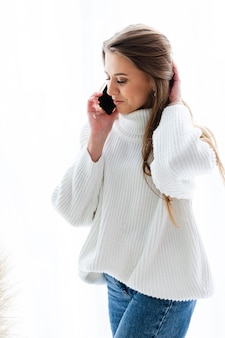 Pretty european woman in casual white sweater sit at home by window with phone, positive talking, having conversation