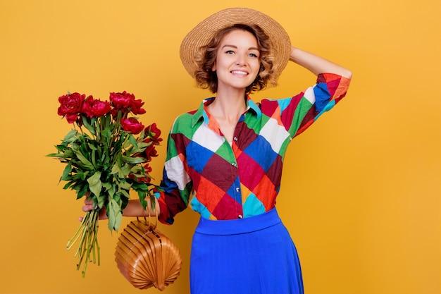 黄色の背景の上に花の花束を持って青いドレスでかなりヨーロッパの女性。麦わら帽子。夏の気分。