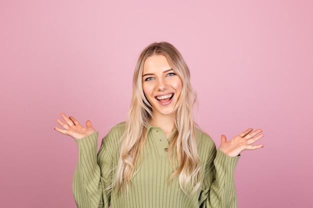 Довольно европейская женщина в повседневном вязаном свитере на розовой стене