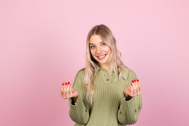 ピンクの壁にカジュアルセーターを着たかなりヨーロッパの女性