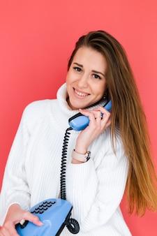 カジュアルな白いセーターでかなりヨーロッパの女性幸せな遊び心のあるポジティブホールディング固定電話笑顔会話をしています