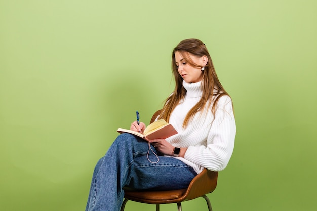 고립 된 캐주얼 흰색 스웨터에 예쁜 유럽 여자, 메모장 및 펜으로 의자에 귀여운 행복 앉아
