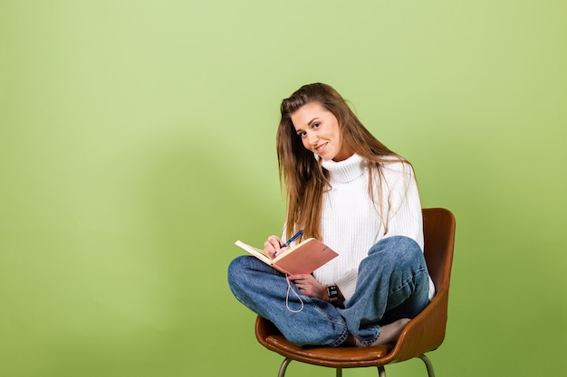 分離されたカジュアルな白いセーターのかなりヨーロッパの女性、メモ帳とペンで椅子に座ってかわいい幸せ