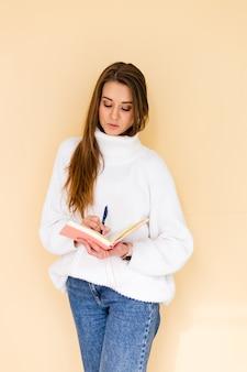 カジュアルな白いセーターのかなりヨーロッパの女性は、メモ帳とペンを保持しているかわいい前向きな思考を分離しました