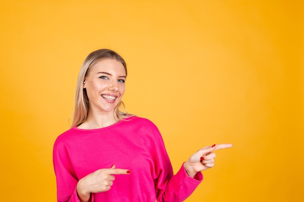 Pretty european woman in pink blouse on yellow wall