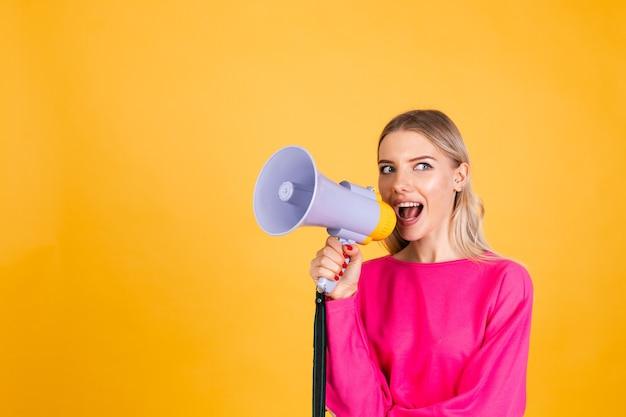 Donna abbastanza europea in camicetta rosa sulla parete gialla