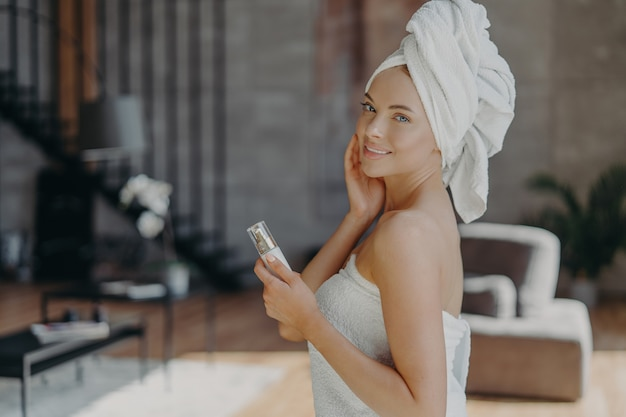 Pretty european woman with healthy glowing skin minimal makeup holds bottle of body lotion