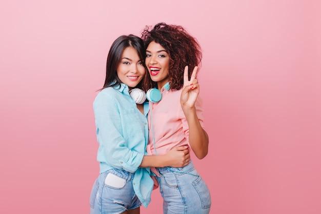 ピンクのシャツでアフリカの女性の友人を優しく抱きしめる短い黒髪のかなりヨーロッパの女性。スリムな巻き毛のムラートの女性はブルネットの白人の女の子を抱きしめます。