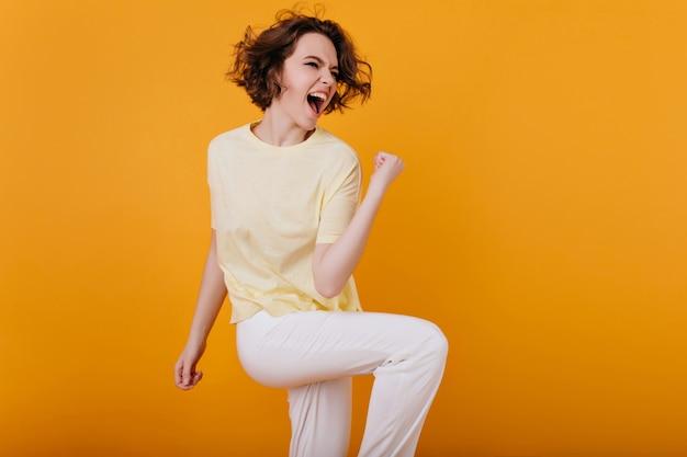 Танцы довольно возбужденной европейской женщины смешные с оранжевым интерьером. фотография в помещении восторженной кудрявой девушки в белом атиире, проводящей время дома.