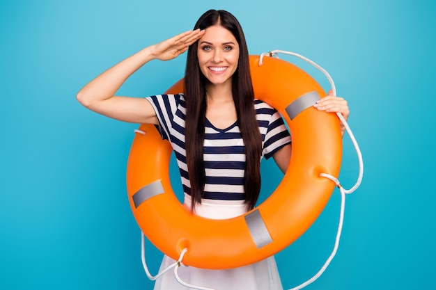 Pretty excited lady hold orange emergency life buoy hand salute