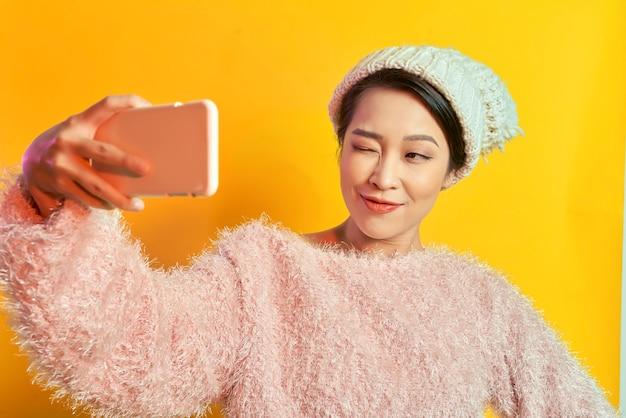 Довольно взволнованная молодая женщина в меховом свитере делает селфи на мобильный телефон, изолированные на ярко-желтом фоне. люди искренние эмоции, концепция образа жизни. рекламная площадка