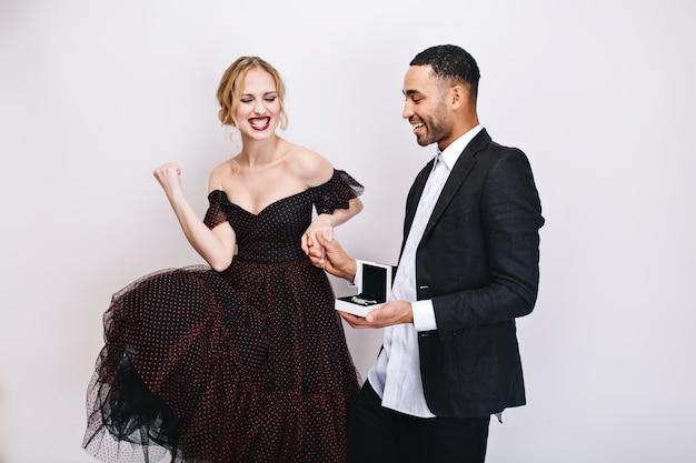 ギフトを持つハンサムな男の近くの明るく幸せな感情を表現する豪華なドレスでかなり興奮している若い女性。素晴らしいプレゼント、笑顔、幸せ、バレンタインデー、恋人。