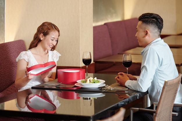 꽤 흥분한 젊은 여성이 레스토랑 테이블에 앉아 있을 때 남자 친구의 하트 모양 상자에 선물을 여는 것