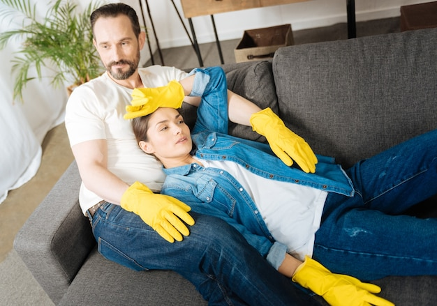 Pretty exhausted sweet couple resting on the couch while wearing gloves and dreaming