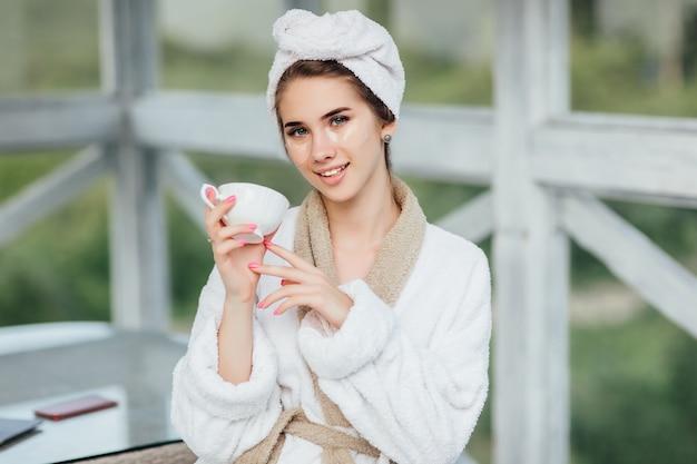 예쁜 얼굴. 흰색 가운을 입고 호텔 테라스에 앉아 커피나 차 한 잔을 들고 있는 매력적이고 웃는 소녀.