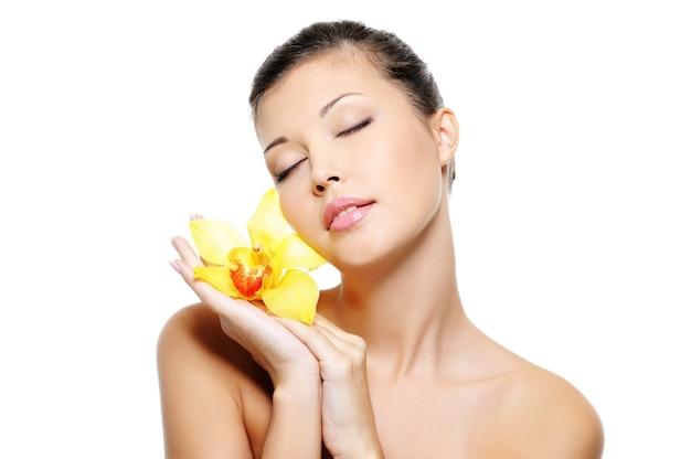Fronte grazioso di una donna asiatica di sensualità di bellezza che tiene fiore sulle sue mani - spazio della copia