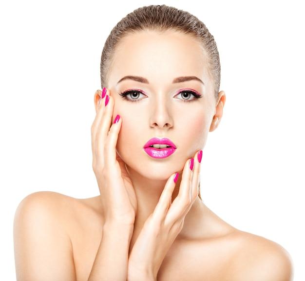 분홍색 눈 화장과 밝은 분홍색 손톱을 가진 아름다운 소녀의 예쁜 얼굴. 흰 벽에 포즈를 취하는 패션 모델