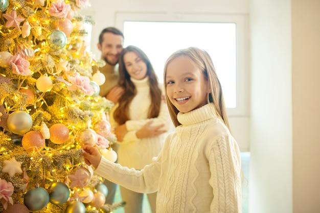 Довольно светловолосая девочка украшает новогоднюю елку со своими родителями