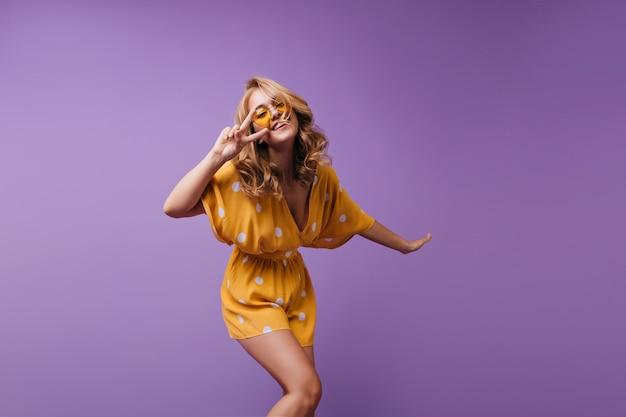 Ragazza abbastanza bionda con la pelle abbronzata divertente ballare e ridere. ritratto di gioiosa signora europea che esprime emozioni positive.
