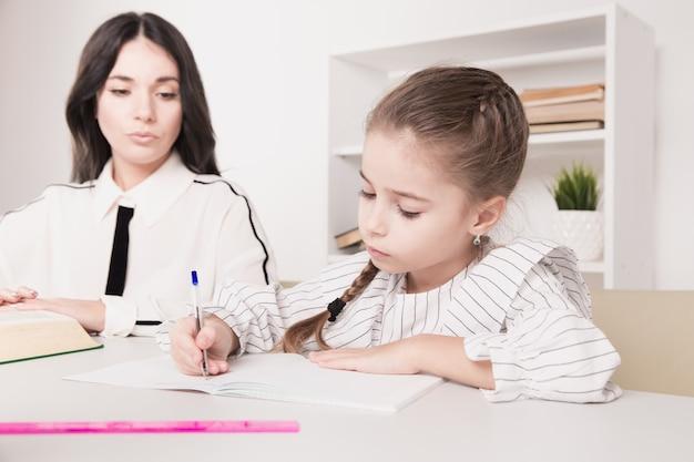 かなり家族の概念。ママと娘が一緒に座って家で勉強しています。