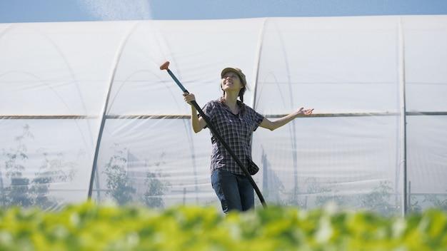 예쁜 농부는 온실 근처 들판에 녹색 어린 묘목을 관개합니다