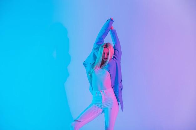 ブレザー、ブラウス、白いジーンズとファッショナブルな服を着た細い体のかわいいファッションブロンドの女の子は、ネオンピンクの光の背景でスタジオで踊っています