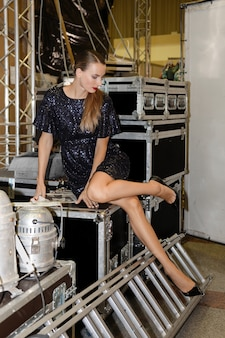 Pretty fashion model looking at her shoe on backstage