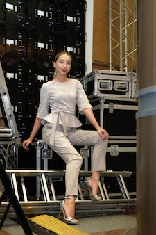 Pretty fashion model sitting among equipment cases on backstage