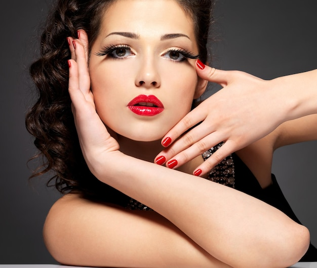 Pretty fashion model with red manicure and lips - brunette woman on black wall