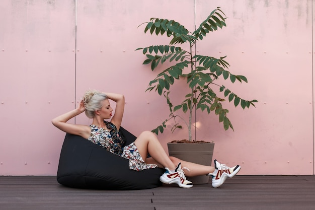 ピンクの壁の近くに座っているスタイリッシュなヴィンテージドレスの赤い唇を持つかわいいファッションモデルの女性